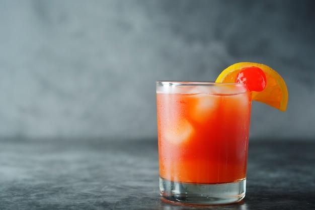 Cocktail estivo succo d'arancia con menta, sciroppo, fette di frutta e ciliegia con ghiaccio.