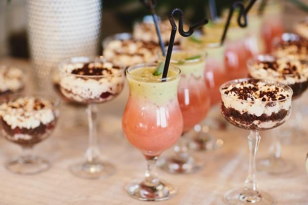 Cocktail freddi estivi con vasca. le limonate differenti con i cubetti di ghiaccio e le fette del limone in barattolo di muratore stanno su una tavola di legno. acqua limonata