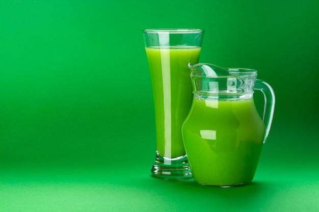 Cocktail fresco del sedano e della mela isolato su verde con lo spazio della copia per testo