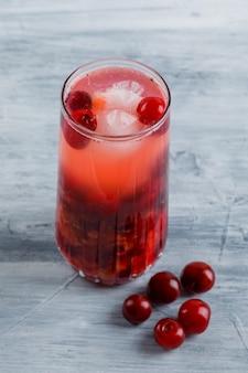 Cocktail ghiacciato di ciliegia in una brocca con ciliegie alte