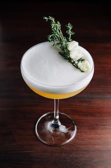 Cocktail giallo con schiuma bianca decorata con fiore bianco e ramo verde. studio.