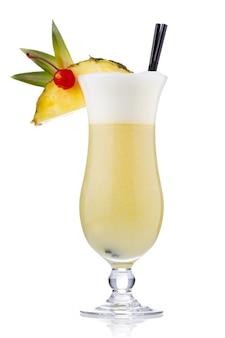 Cocktail giallo latte con frutti di bosco e fetta di ananas isolato
