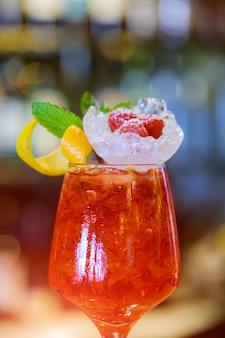 Cocktail guarnito con calce in piedi sul bancone del bar.