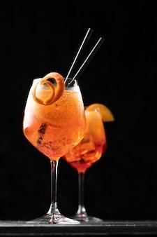 Cocktail italiano classico dello spritz dell'aperol in vetro sul nero, fine su