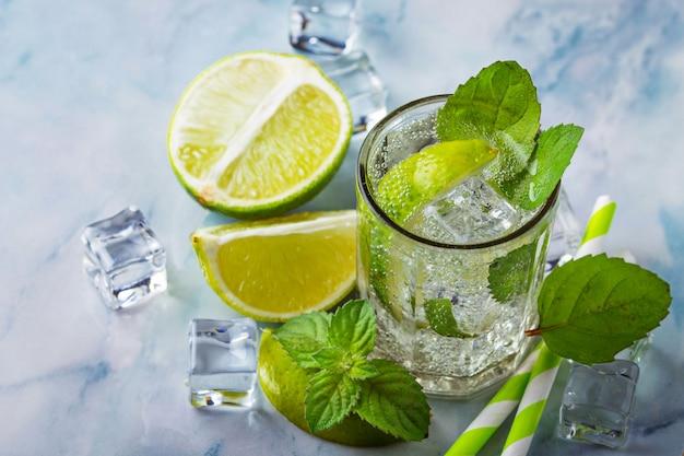 Cocktail mojito con menta, lime e ghiaccio. messa a fuoco selettiva