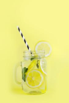 Cocktail rinfrescante di estate con il limone, la menta e il ghiaccio in barattolo di muratore su giallo.