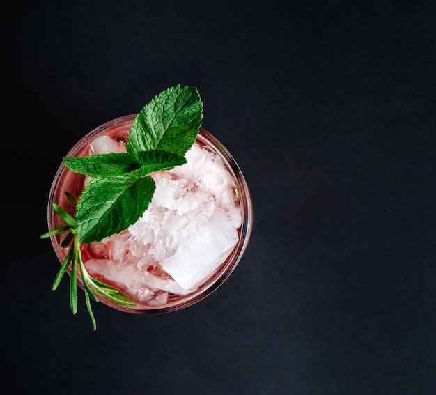 Cocktail rosa con la vista superiore del primo piano del rosmarino e della menta