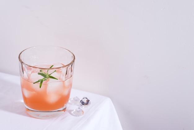 Cocktail rosa con rosmarino e ghiaccio in vetro su una tovaglia bianca sul tavolo