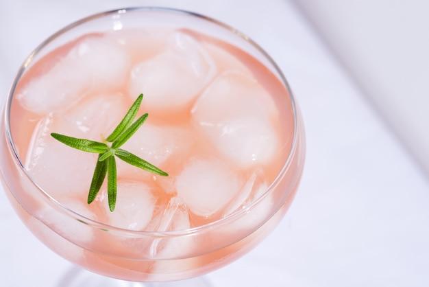 Cocktail rosa con rosmarino e ghiaccio su un primo piano bianco della tovaglia