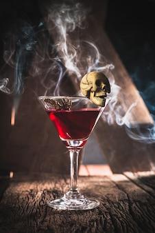 Cocktail rosso con il concetto del partito di halloween del cranio