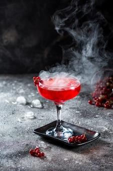Cocktail rosso con vapori di ghiaccio.