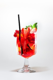 Cocktail rosso rinfrescante con contorno di frutti di bosco, lime e menta