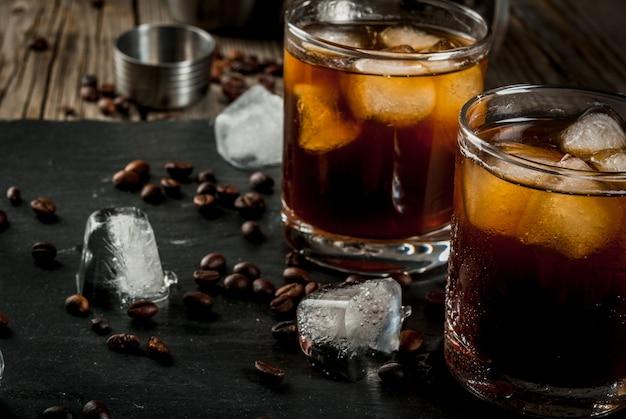 Cocktail russo nero ubriaco con liquore del caffè e della vodka sulla tavola di legno rustica
