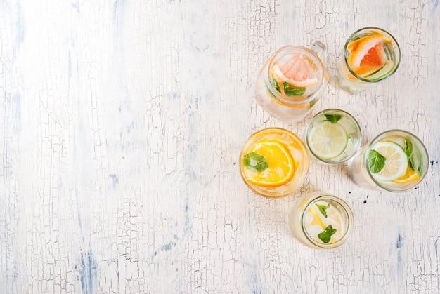 Cocktail salutari estivi, insieme di varie acque infuse di agrumi, limonate o mojitos, con pompelmo lime e arancio, bevande disintossicanti dieta, in diversi bicchieri luce sfondo copia spazio