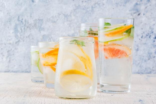 Cocktail salutari estivi, set di varie acque infuse di agrumi, limonate o mojito, con lime pompelmo e arancio, bevande disintossicanti dietetiche, in diversi bicchieri