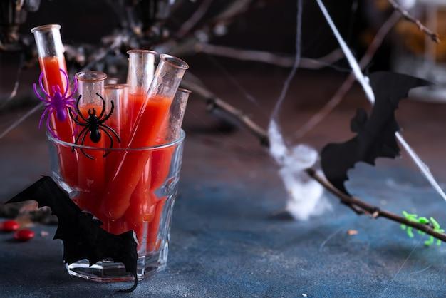 Cocktail sanguinante in tubi di vetro per la celebrazione della festa di halloween.