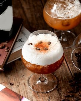 Cocktail spumoso alla cannella condito con chicchi di caffè e polvere di cannella