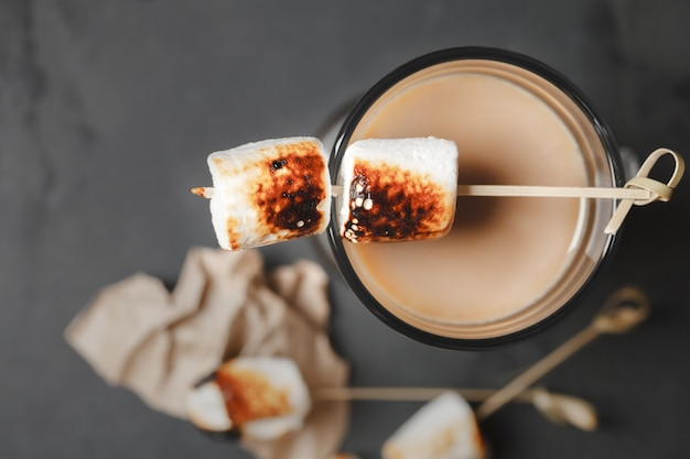 Cocktail tradizionali autunnali e invernali, alcolici. cocktail di cioccolata calda da falò con marshmallow arrosto. marshmallow al latte al cacao