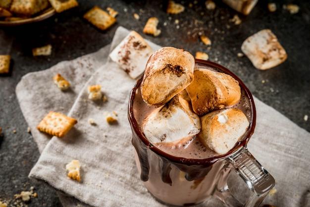 Cocktail tradizionali autunnali e invernali, alcolici. cocktail di zabaione al cioccolato caldo falò con cracker salati e marshmallow arrosto, in due tazze, sul tavolo di pietra nera,