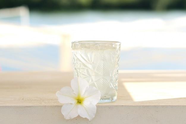 Cocktail trasparente in un bicchiere di vetro. limonata. decorazioni floreali
