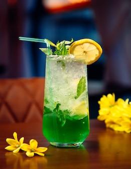 Cocktail verde con menta, cubetti di ghiaccio e fetta di limone.