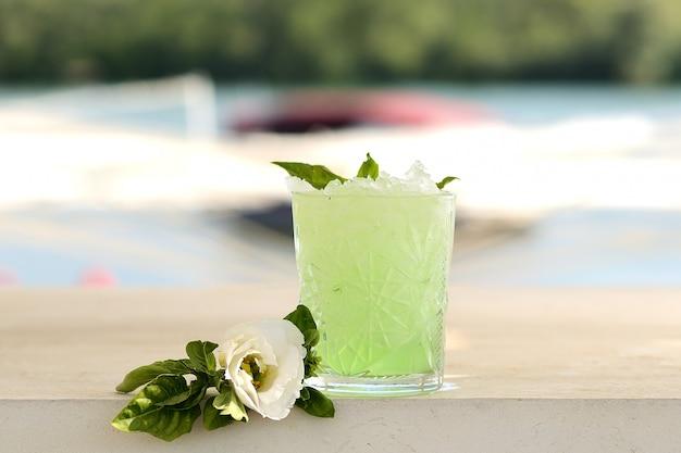 Cocktail verde con menta e ghiaccio in un bicchiere di vetro. con decorazioni floreali