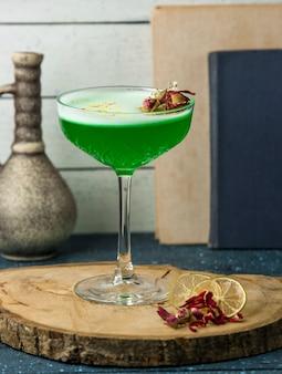 Cocktail verde guarnito con boccioli di rosa essiccati in cristallo