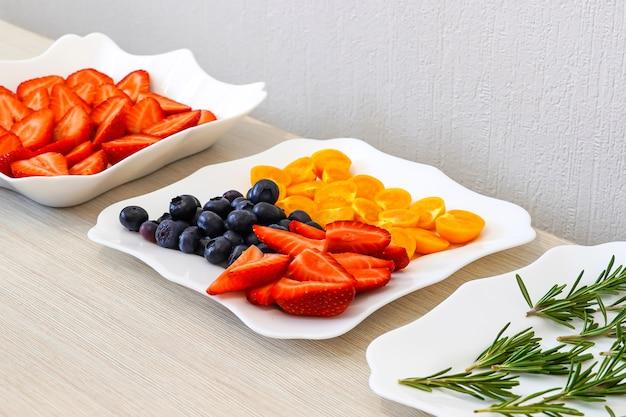 Cocktail vitaminico di frutti di bosco e frutta. fragole, mirtilli, rosmarino e physalis. decorazione per una torta festiva con prodotti naturali.