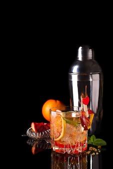 Coctail arancia sanguinella con ghiaccio e menta isolata sul nero