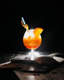 Coctail arancione con ghiaccio di succo d'arancia fresco e cannucce sul libro
