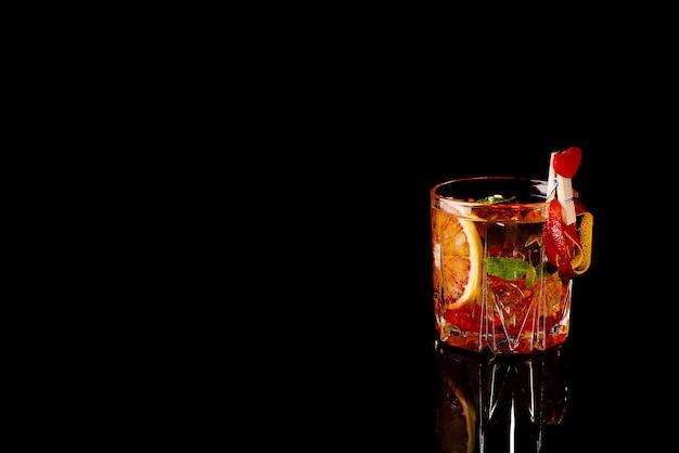 Coctail di arancia sanguinella con ghiaccio e menta sul nero