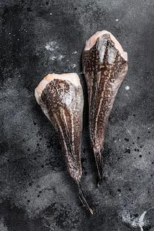 Coda di rospo cruda senza testa. superficie nera. vista dall'alto