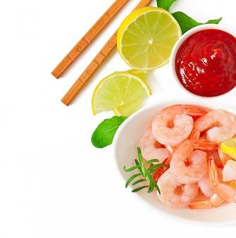 Code di gamberi con limone e rosmarino freschi in una ciotola bianca