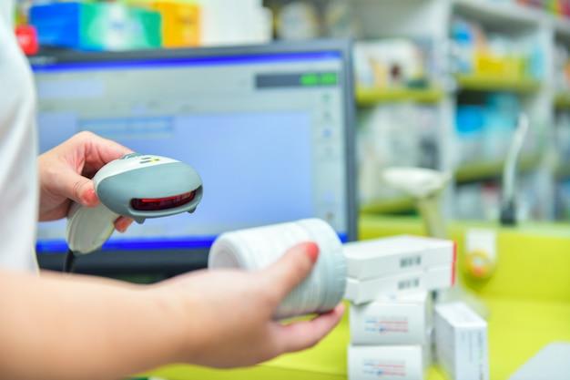 Codice a barre di scansione del farmacista della droga della medicina in una farmacia della farmacia.