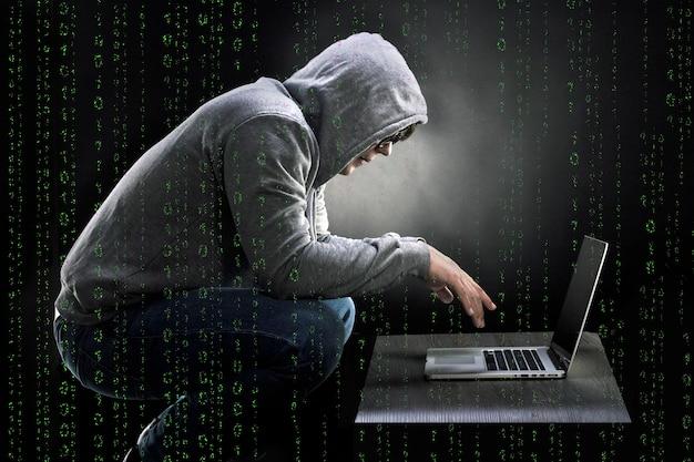 Codice binario con uomo accovacciato su una sedia e guardando in un laptop, il concetto di un programmatore pazzo