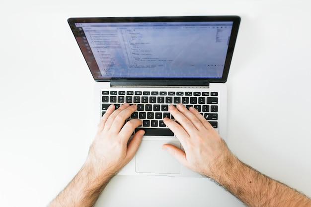 Codifica del primo piano sullo schermo, mani dell'uomo che codifica html e programmazione su schermo portatile, sviluppo web, sviluppatore
