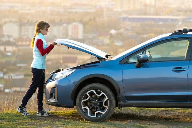Cofano di apertura della giovane donna dell'automobile ripartita che ha problemi con il suo veicolo