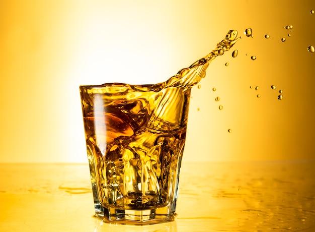 Cognac in un bicchiere splash isolato su sfondo con la riflessione