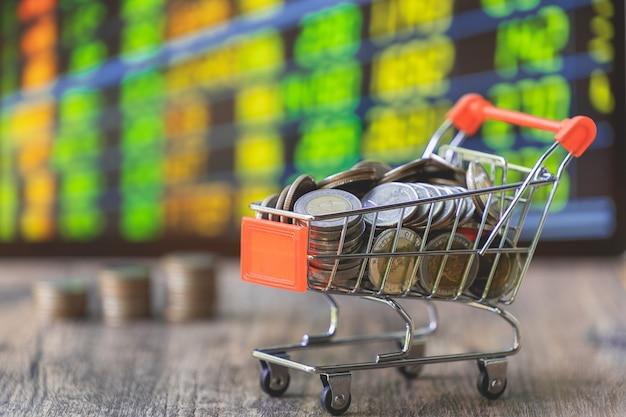Coin nel carrello della spesa con bordo del mercato azionario