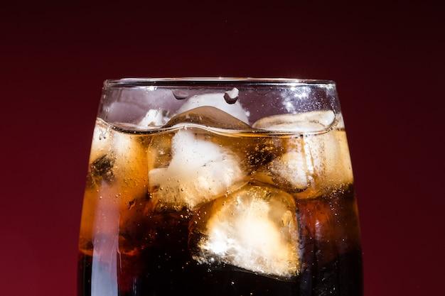 Cola con cubetti di ghiaccio in un bicchiere di close-up