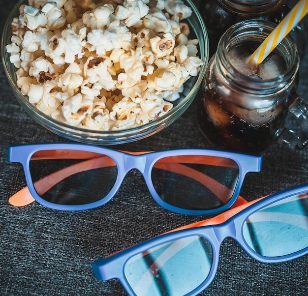 Cola con ghiaccio, popcorn in una ciotola trasparente e occhiali 3d