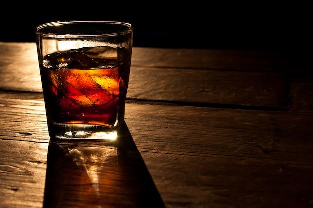 Cola con whisky e ghiaccio su uno sfondo di tavolo in legno