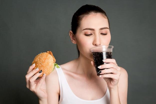 Cola della bevanda della giovane donna e hamburger della tenuta su fondo grigio. cibo spazzatura e concetto di fast food