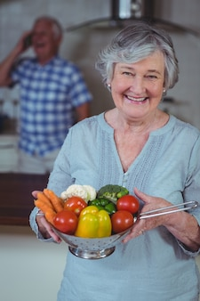 Colapasta senior felice della tenuta della donna con le verdure