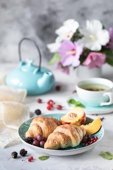 Colazione a base di bacche fresche e frutta con cornetti, tè con un bouquet di fiori estivi.