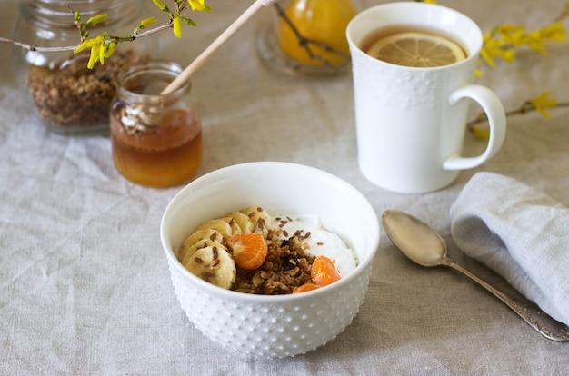Colazione a base di muesli con yogurt e tè e fiori di forsizia su una tovaglia di lino. stile rustico.