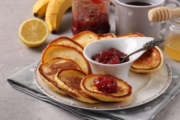 Colazione a casa. frittelle con marmellata, miele, banane e una tazza di caffè sul tovagliolo grigio su sfondo concreto