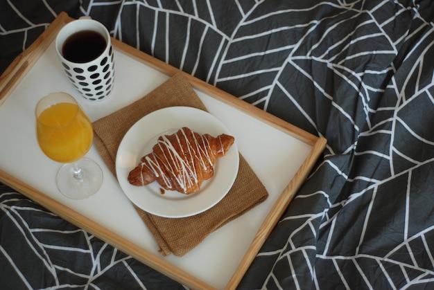 Colazione a letto. caffè, croissant e bicchiere di succo d'arancia.