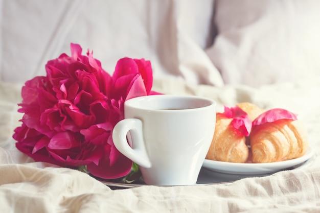 Colazione a letto con tazza di caffè, cornetti e fiori