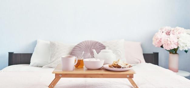 Colazione a letto nella camera d'albergo. alloggio. faccia colazione a letto con la tazza di tè con i pancake sul vassoio sul letto